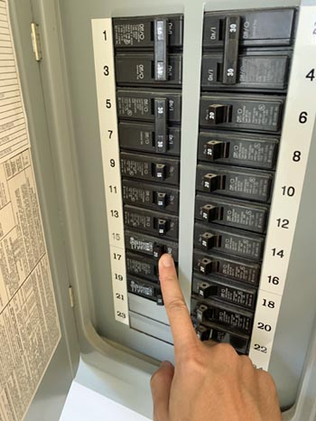 This pictures shows an electrical panel upgrade in Parker Co. The electrician is testing the circuit breaker.